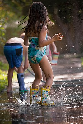 Children playing with water hose on sidewalk - p924m1125687f by Kinzie Riehm
