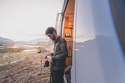 A man standing beside a van looking down at a camera in his hands, rocky landscape in the background. - p924m2186229 by Alex Eggermont