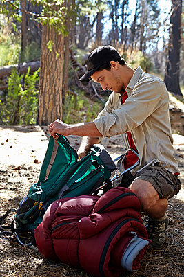 Young man in forest unpacking camping equipment, Los Angeles, California, USA - p924m998790f by Tony Garcia