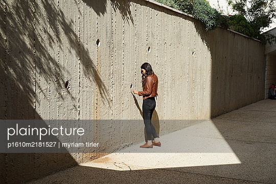 young girl standing by a wall - p1610m2181527 by myriam tirler
