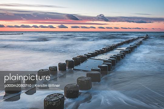 Germany, Mecklenburg-Western Pomerania, Darss, Ahrenshoop, West beach, groyne in evening light - p300m2080710 by Kerstin Bittner