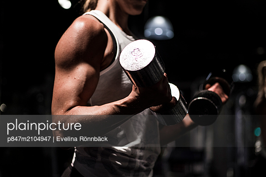 Woman Doing Bicep Exercise In Gym   - p847m2104947 by Evelina Rönnbäck