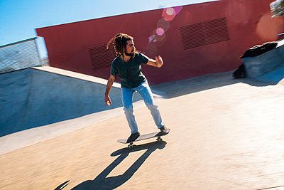 Young man with dreadlocks skateboarding in a skatepark - p300m1120796f by Kiko Jimenez