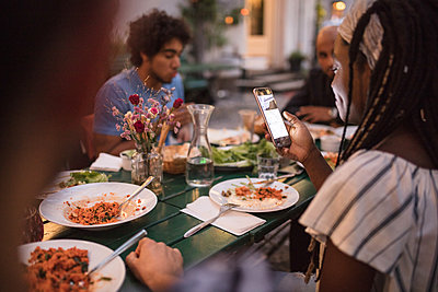 Young woman using mobile phone while having dinner with friends during garden party - p426m2046194 by Maskot