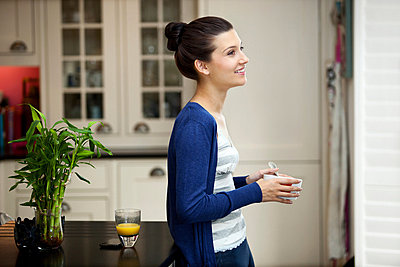 Young woman eating breakfast - p924m711139f by Franek Strzeszewski