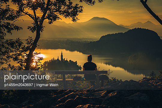 Person watching an early morning sunrise at Lake Bled - p1455m2043697 by Ingmar Wein