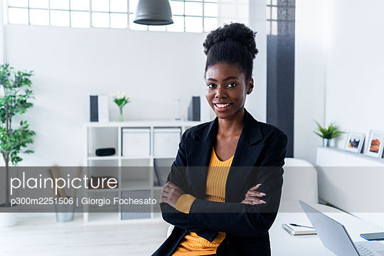 Smiling young Afro businesswoman with arms crossed in office - p300m2251506 by Giorgio Fochesato