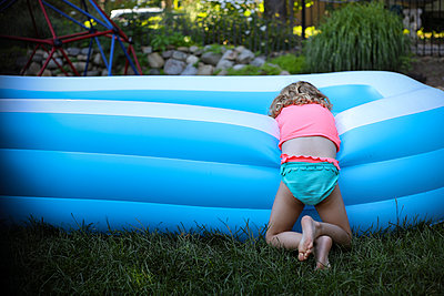 Rear view of girl leaning on blue wading pool at backyard - p1166m2105975 by Cavan Images
