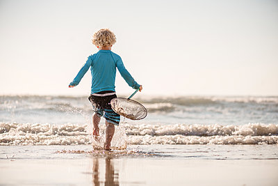 Back view of toddler boy holding net running to the waves at a beach - p1166m2108124 by Cavan Images