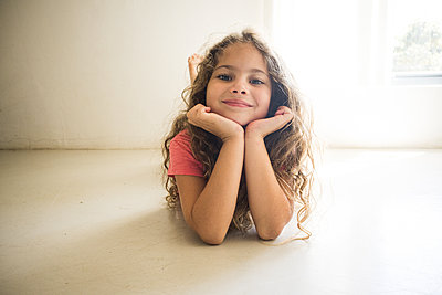 Little girl with curly hair lying on the floor - p1640m2246134 by Holly & John