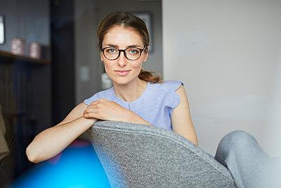 Portrait of smiling woman wearing glasses sitting on armchair - p300m1580980 von Philipp Nemenz