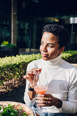 Smiling businesswoman day dreaming while drinking juice at restaurant during sunny day - p300m2241849 by Katharina und Ekaterina
