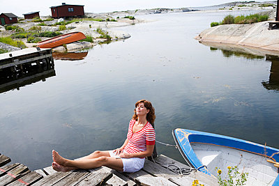 A woman sitting on a jetty in the archipelago of Stockholm Sweden. - p31219957f by Plattform