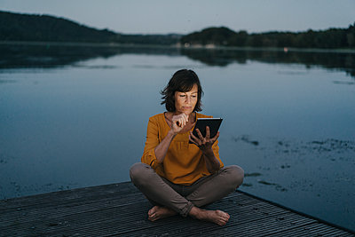 Woman uses tablet computer on jetty at Lake Baldeneysee - p586m1172063 by Kniel Synnatzschke