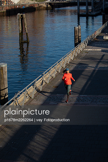 Woman jogging in Hamburg - p1678m2262264 by vey Fotoproduction