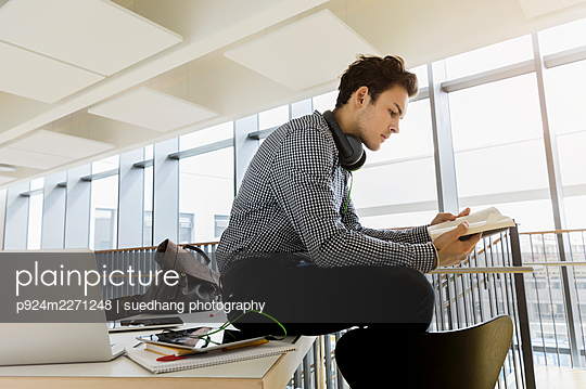 Germany, Bavaria, Munich, Young man sitting on desk and reading book - p924m2271248 by suedhang photography