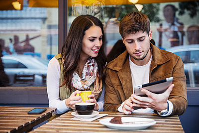 Couple using tablet computer while sitting at cafe - p1166m1204403 by Cavan Images