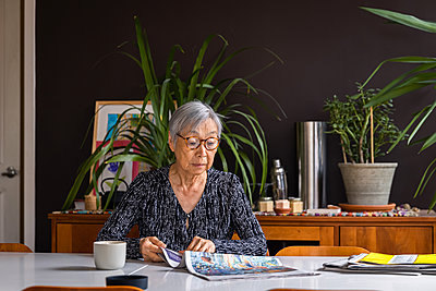 Senior woman reading newspaper while sitting at table with coffee - p1166m2285613 by Cavan Images