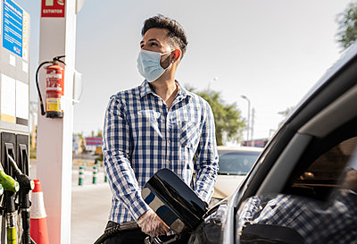 Man with face mask refueling gas in car at station - p300m2299169 von Jose Carlos Ichiro