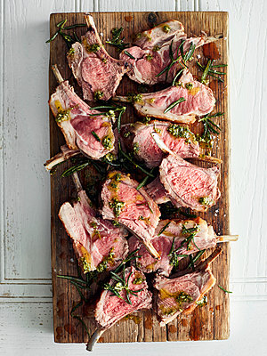 Overhead view of roasted lamb cutlets on cutting board with  rosemary - p429m1417655 by Debby Lewis-Harrison
