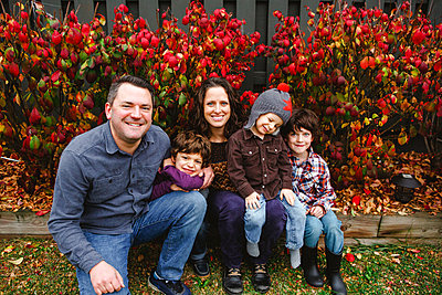 A smiling family sit together on wooden log in front of red leaves - p1166m2112922 by Cavan Images