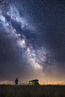 Silhouette of climber standing next to the tent watching the stars - p1166m2136889 by Cavan Images