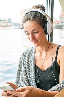Smiling young woman listening music with headphones looking at her cell phone - p300m1175936 by A. Tamboly