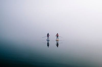 Two women stand up paddle surfing on a lake in the fog - p300m2166601 by Daniel González