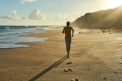 Man jogging on sand at beach during sunset - p300m2227336 by Veam