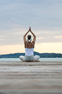 Frau macht eine Yogaübung auf einem Steg an einem See - p4903139 von T-Pool
