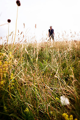 Man standing in meadow looking at camera - p597m2108584 by Tim Robinson