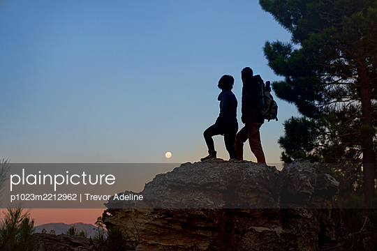 Silhouette young hiker couple enjoying view of moon from rock at dusk - p1023m2212962 by Trevor Adeline