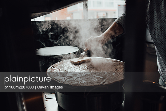 Hand of chef buttering hot crepes while cooking at restaurant kitchen - p1166m2207890 by Cavan Images