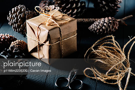 Package wrapped in kraft paper and tied with string - p1166m2235330 by Cavan Images