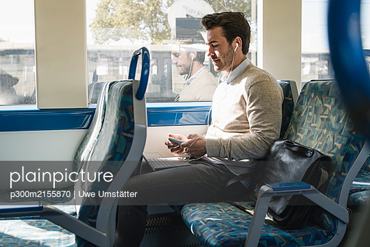 Young man with earphones using smartphone and tablet on a train - p300m2155870 by Uwe Umstätter