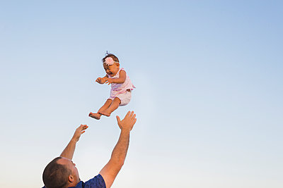 Low angle view of father throwing daughter into air against clear sky - p1166m1423319 by Cavan Images