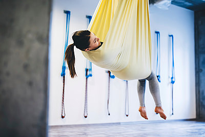 Young woman hanging in hammock while practicing yoga at gym - p1166m1576471 by Cavan Images