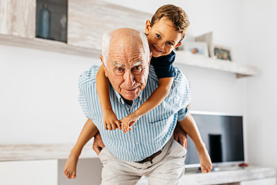 Portrait of grandfather giving his grandson a piggyback ride in the living room - p300m2029413 by Josep Rovirosa