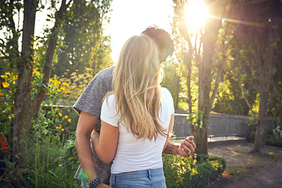 Happy young couple embracing and kissing in a park in summer - p300m2043035 by Martina Ferrari