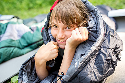 Smiling girl, wrapped in sleeping bag, portrait - p300m2160373 von Fotoagentur WESTEND61
