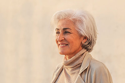 Smiling mature woman contemplating by beige wall - p300m2281482 by PICUA ESTUDIO