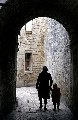 Woman with child in old town alley - p6440684 by Rob Penn
