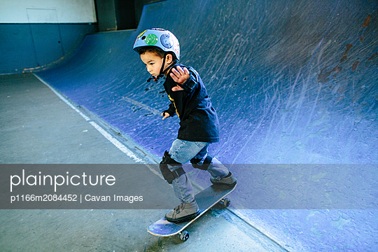 Skater kid skateboarding down a blue ramp - p1166m2084452 by Cavan Images