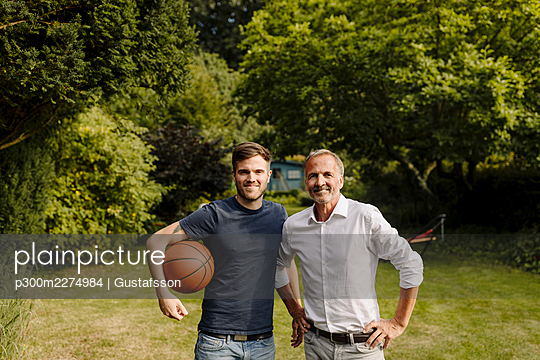 Son holding basketball while standing by father in backyard - p300m2274984 by Gustafsson
