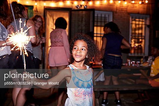 Smiling girl holding burning sparkler at backyard party - p555m1303238 by Granger Wootz