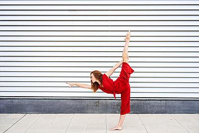 Sporty young woman doing acrobatics outdoors - p300m2140189 by Javier Sánchez Mingorance