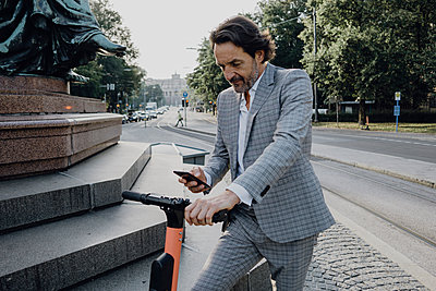 Businessman renting an e-scooter in the city - p300m2140515 by Johanna Lohr