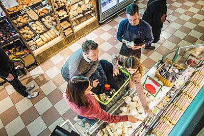 High angle view of family choosing food packets from shelf by owner in store - p426m2097558 by Maskot