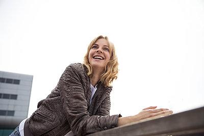 Junge Frau lehnt an einem Geländer - p788m1466158 von Lisa Krechting