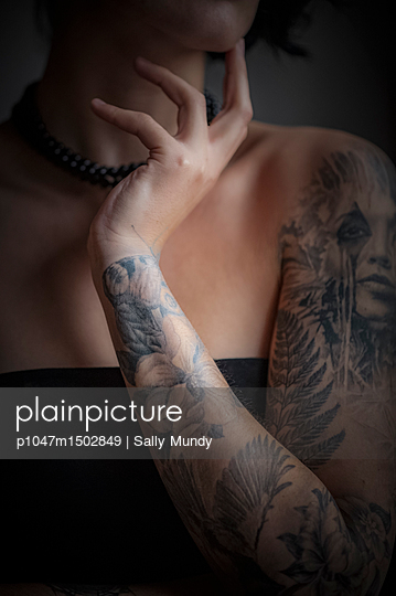 Tattoed womans arm with hand on chin - p1047m1502849 by Sally Mundy